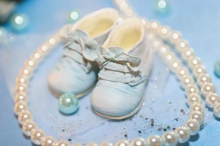 Graziose scarpe da bambino con collana di perle attorno: i piccoli passi che ognuno di noi guidato dagli Angeli fa verso la luce