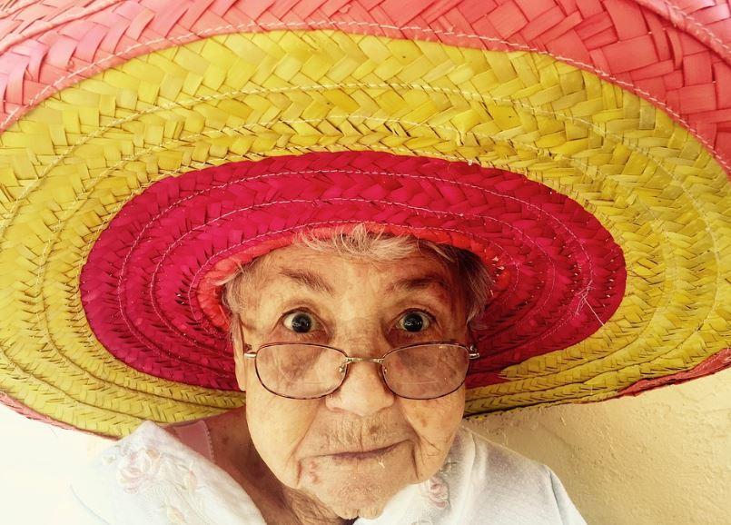 Una anziana donna con occhiali occhi sgranati e un bel grande cappello di paglia colorato. Cosa pensano di lei gli Angeli?